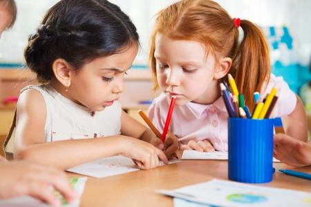 Schattige kleuters tekenen met kleurrijke potloden op kinderdagverblijf