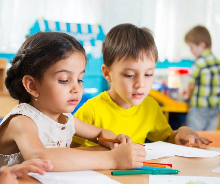 preschool children: Cute preschoolers drawing with colorful pencils at daycare
