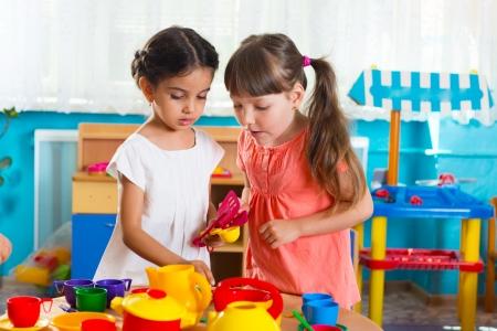 Twee schattige kleine meisjes spelen rol spelen in de kinderopvang Stockfoto
