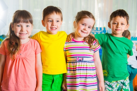 Group of four hapy preschoolers standing in playroom