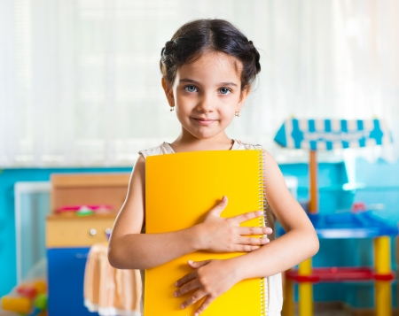 beautiful indian girl face: Beautiful little latin girl portrait with book in daycare