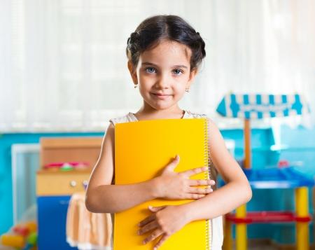 niño escuela: Hermosa niña retrato latino con el libro en la guardería Foto de archivo