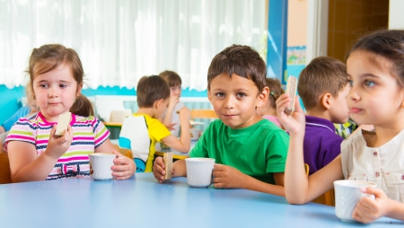 Cute little children drinking milk at daycare photo