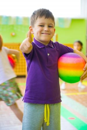 Schattige kleine jongen spelen op kinderdagverblijf gymnastiek met bal