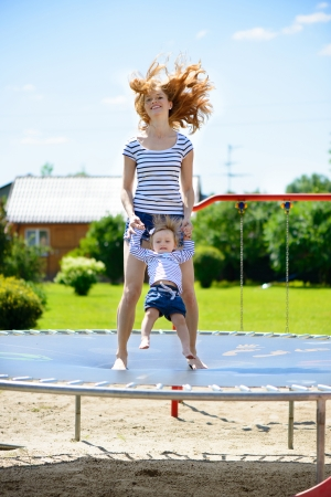 Beautiful young mother and little daughter bouncing on trampoline photo