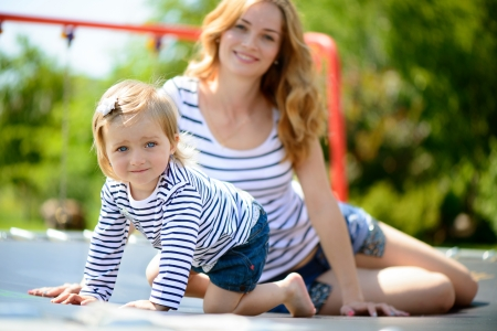 Beautiful young mother and little daughter playing at playground Stock Photo