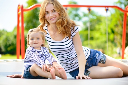 Beautiful young mother and little daughter playing at playground photo