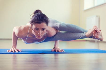Beautiful young woman yoga workout in gym photo