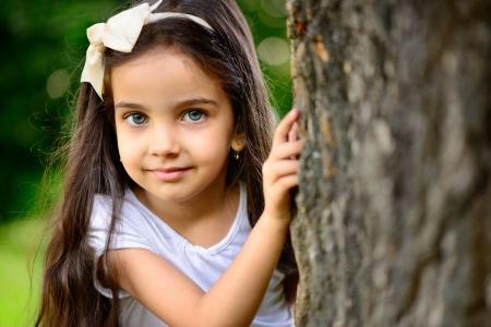 ojos azules: Retrato de niña hispana con profundos ojos azules en el parque soleado