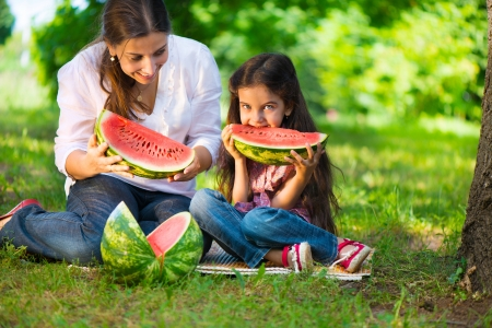 Watermelon: Happy hispanic family eating watermelon at park Stock Photo