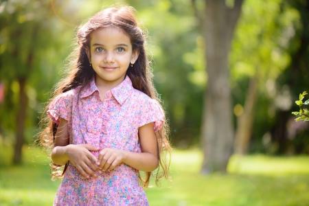 日当たりの良い公園の深い青色の目とヒスパニック系の女の子の肖像画
