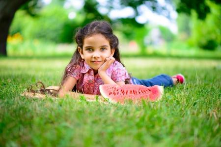 Cute hispanic girl eating watermelon at park photo