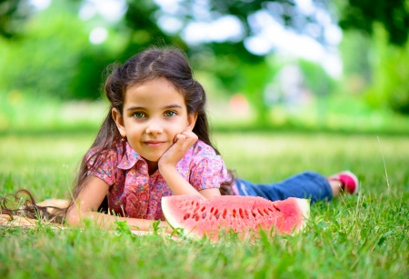 Cute hispanic girl eating watermelon at park photo
