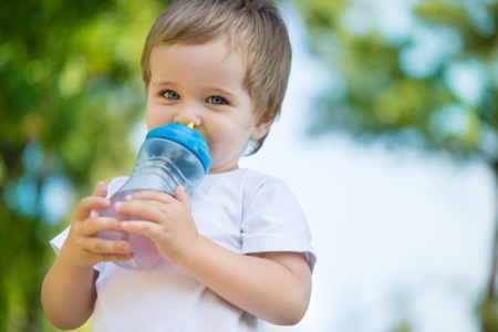 Cute little boy drinking water from feeding bottle photo