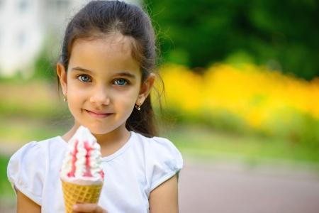 Cute hispanic little girl with ice-cream at park