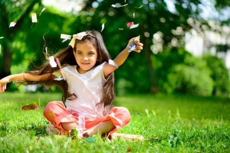 disfrutar: Muchacha hisp�nica linda tirar confeti en el parque