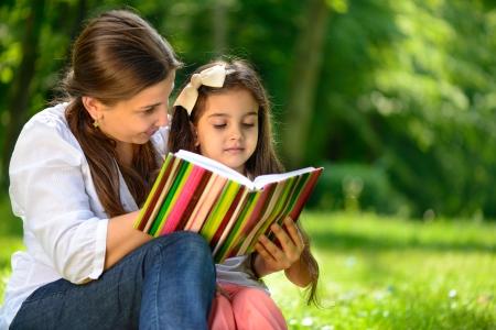 niños leyendo: Feliz libro de lectura familiar latino en el parque