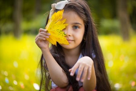 niños latinos: Hispánico lindo niña que oculta sobre la hoja amarilla