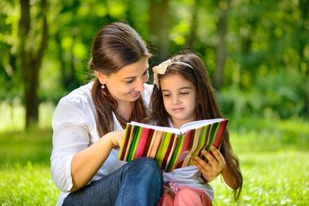 niños leyendo: Madre joven feliz con su hija en el parque