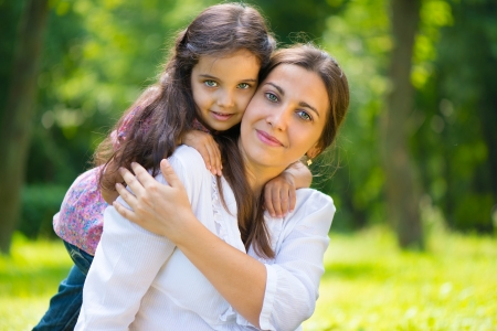 daughters: Happy young mother with her daughter at park Stock Photo