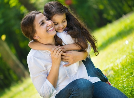 latin child: Happy young mother with her daughter at park Stock Photo