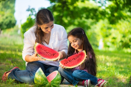 indian summer seasons: Happy indian family eating watermelon in park