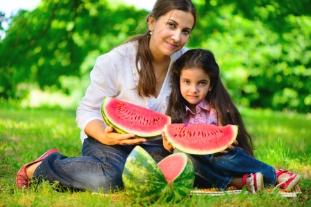 lies down: Happy indian family eating watermelon in park