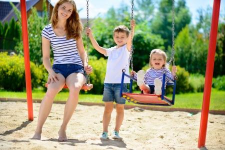 columpios: Feliz madre y sus hijos en el parque