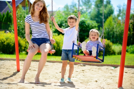 Happy mother and her children on playground photo