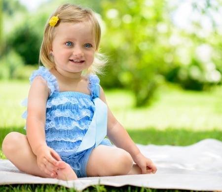 rozkošný: Cute usmívající se holčička sedí na trávě