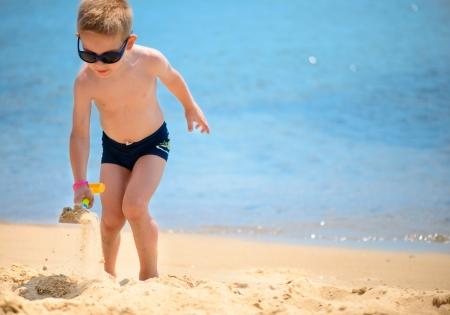 pantalones cortos: Lindo niño jugando con la arena en la playa del océano