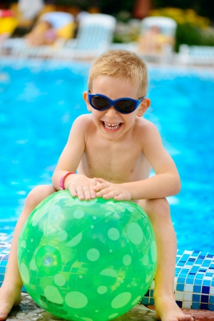 child ball: Cute little boy in sunglasses sitting at swimming pool Stock Photo