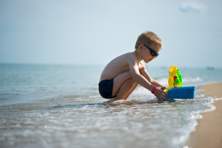 Little boy in sunglasses playing with toy boat at ocean beach photo