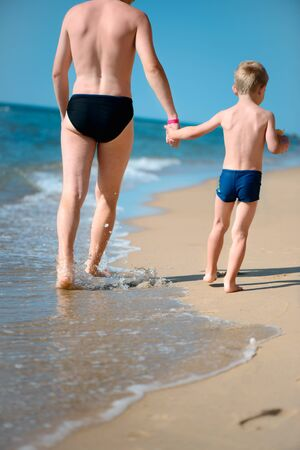 Young father and little son walking at ocean beach. Rear view photo
