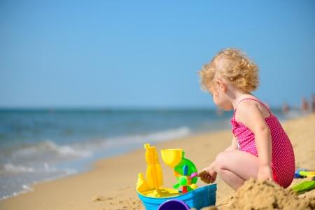 beach toys: Cute little girl playing with sand at ocean beach
