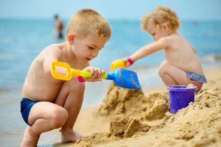 Broertje en zusje spelen met zand op oceaan strand