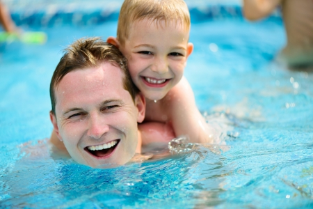 Young father with little son swimming in pool photo