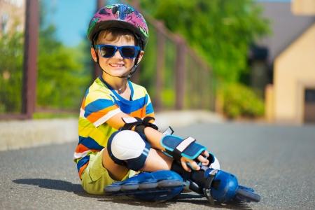 patinar: Niño lindo en gafas de sol y casco con rodillos
