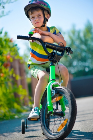 Cute little boy in helmet riding bicycle photo