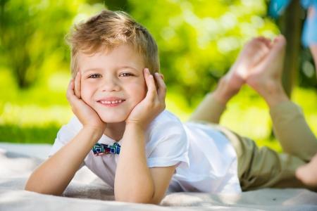 Schattige kleine jongen met vlinder liggen op groen gras in het park