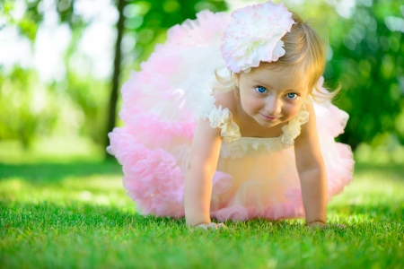 Cute little girl in tutu on green grass photo