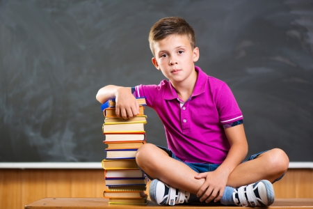 boy sitting: Cute school boy sitting with books against blackboard in classroom