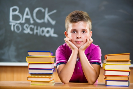 Cute pupil with pile of books in classroom photo
