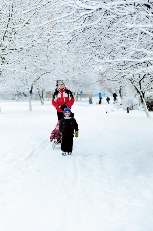 Father and children pulling sledge in snowy alley photo