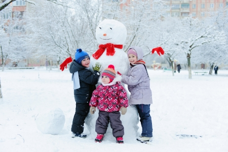 Happy beautiful children building snowman in garden photo