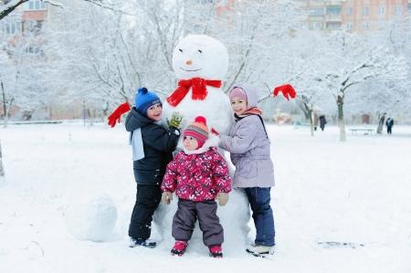 fille hiver: Happy beaux enfants construisant bonhomme de neige dans le jardin Banque d'images