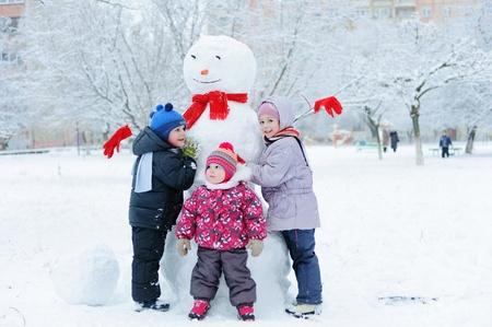 Happy beautiful children building snowman in garden photo