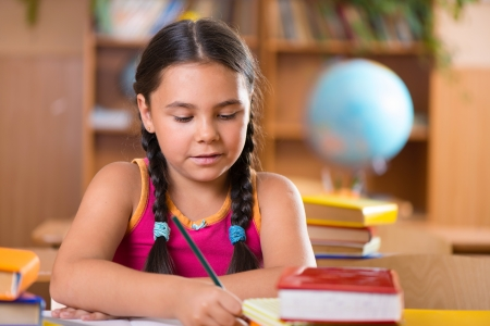 writing activity: Cute hispanic girl writing in notebook in classroom at school