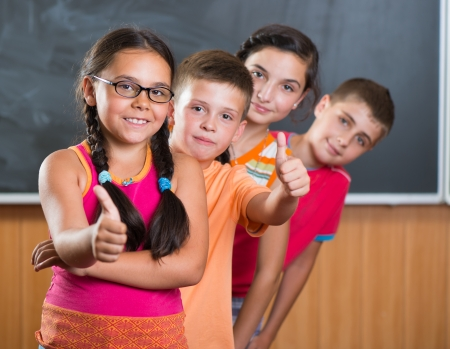 Four smiling schoolchildren standing in classroom against blackboard photo