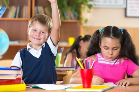 Cute schoolchildren during lesson in classroom at school Standard-Bild
